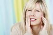 Frau hält sich die Backe bei Zahnschmerzen