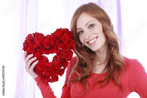 Glückliche Frau rotem Rosenherz