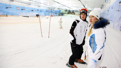 instructor with girl waiting till other people go down to ski on