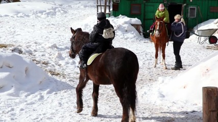 Boy sits horseback, woman help his sister to climb on horse