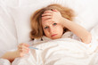 Woman with thermometer sick colds, flu, fever in bed