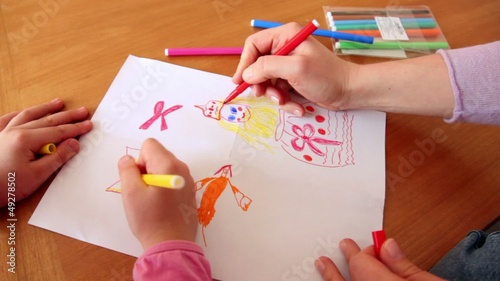 Woman and little girl draw princess on paper with colored