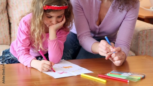 Mother with daughter sit on sofa at wooden table and draw with