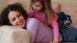 Little girl lies on mother legs and kisses her cheek, closeup