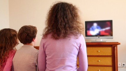 Mother with kids boy and little girl sit watch tv