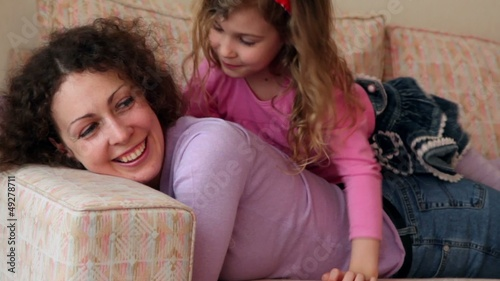 Little girl lies on mother legs and kisses her cheek, closeup