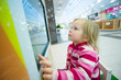 Adorable girl play computer game with touchscreen in supermarket