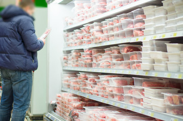 Customer select beef slices in plastic boxes on shelves in super
