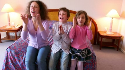 Mother and her kids boy and girl sit on sofa and clap hands when