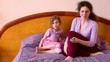 Mother and daughter sit on bed and watch tv with remote control