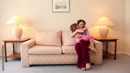 Little girl runs to her mother sit on sofa at room with lamp on