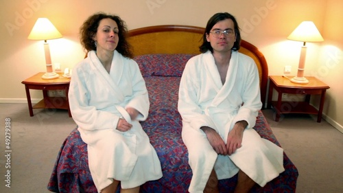 Man with woman in bathrobes come to bedroom and sit on bed