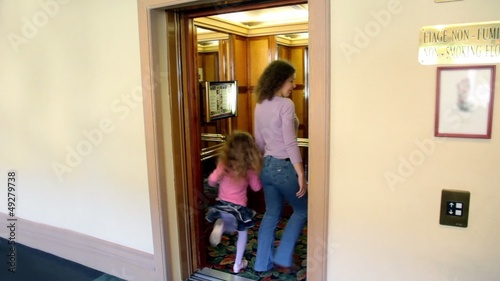 Doors opens and mother with daughter walk in elevator