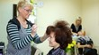 To woman of average years hairdresser does hairdress and fasten