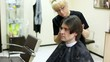 Hairdresser cuts hair to man with long hair by clipper