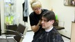 Hairdresser cuts hair to man with long hair