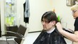 Hairdresser cuts hair on nape to man with long hair by clipper
