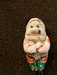 Old gnome on fine tilth soil background