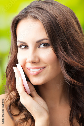 Woman cleaning skin by cotton pad, outdoor