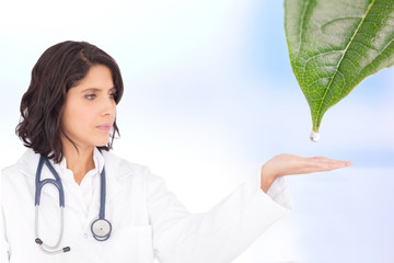 Doctor reaching out to dew drop falling from leaf