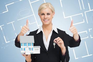 Multi-tasking estate agent holding keys and model home while giv