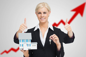 Multi-tasking estate agent holding keys and model house while gi