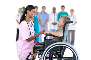 Nurse chatting with little boy in wheelchair