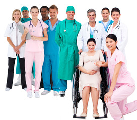 Nurse with pregnant woman in wheelchair with medical staff