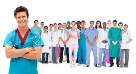 Smiling surgeon in front of a team of doctors standing together