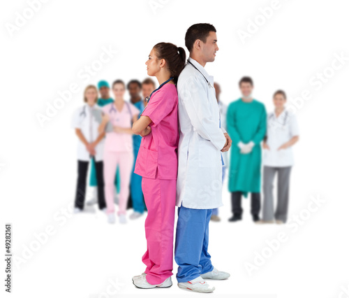 Doctor and nurse standing back to back