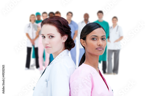 Serious doctor and nurse standing back to back