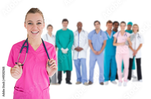 Smiling nurse with medical staff behind her