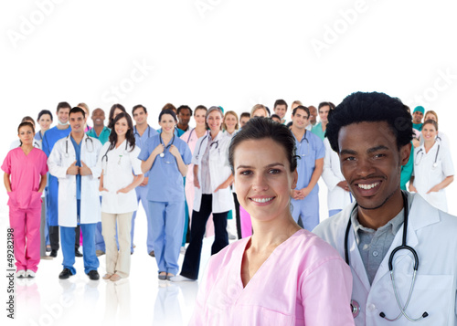 Smiling doctors in front of a team of doctors standing together
