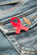 Aids awareness ribbon pinned on to jeans pocket