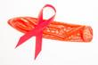 Red awareness ribbon lying on condom