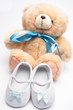 Teddy bear with blue ribbon and white booties