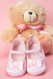 Pink baby booties and teddy bear
