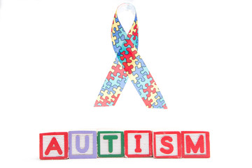 Autism awareness ribbon above letter blocks spelling autism