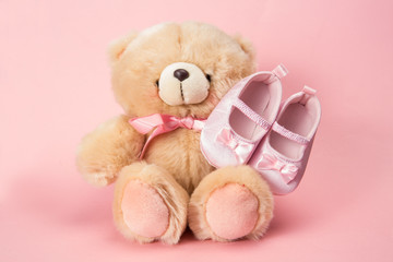 Fluffy teddy with pink ribbon and baby booties
