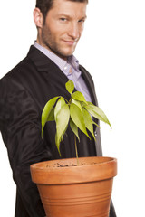 smiling man holding pot with a tree on white background