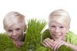 canvas print picture - Zwei Kinder schauen zwischen Grasbüscheln durch