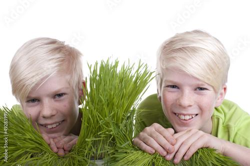 canvas print picture Zwei Kinder schauen zwischen Grasbüscheln durch