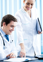 Two happy medical people working at office