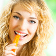 Young woman eating carrots
