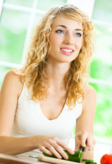 Young cheerful blond woman making salad