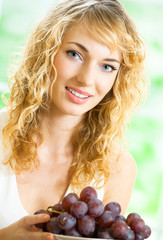 Young happy woman with plate of grape