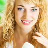 Happy smiling woman applying creme, indoor