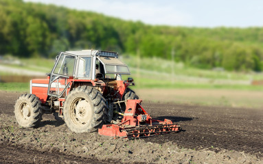 Red tractor working the ground in spring