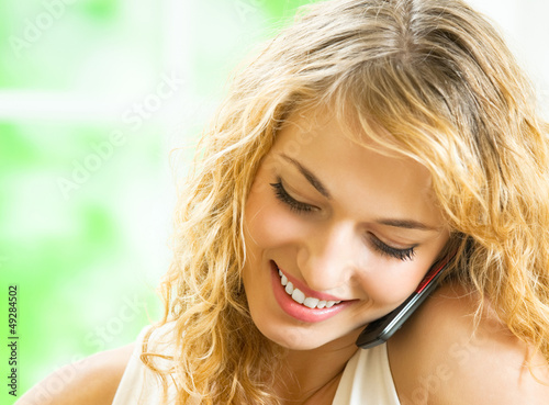 Happy smiling woman talking on cellphone
