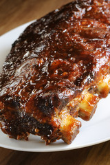 Grilled juicy barbecue pork ribs in a white plate.